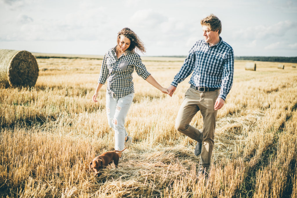 Young couple holding hands while walking through field at sunny day.